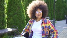 Afrikanische Frau des Porträts mit einer Afrofrisur behindert in einem Rollstuhl in den Glasfahrten im sonnigen Park stock video
