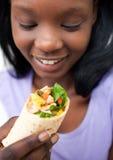 Afrikanische Frau, die einen Fajita isst Lizenzfreies Stockfoto
