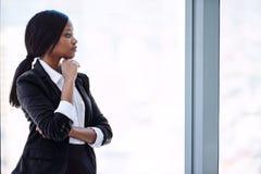 Afrikanische Geschäftsfrau, die heraus Fenster im Gedanken über Investitionen schaut Lizenzfreie Stockbilder