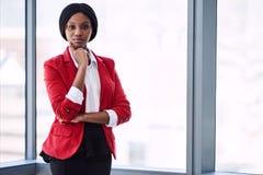 Afrikanische Geschäftsfrau, die sicher Kamera beim Tragen des roten Blazers untersucht Stockbilder