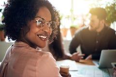 Afrikanische Geschäftsfrau, die während einer boardoom Sitzung in von lächelt lizenzfreies stockbild