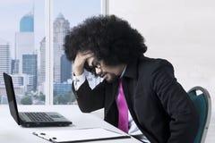 Afrikanische Geschäftsmanngefühlskopfschmerzen im Büro Lizenzfreie Stockfotografie
