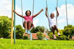 Afrikanische Kinder, die auf Schwingen in der Nachbarschaft spielen