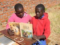 Afrikanische Kinder, die ein Bibelgeschichtenbuch lesen stockbild