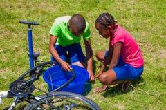 Afrikanische Kinder, die ein Durchbohren auf einem Fahrrad regeln stockfotografie
