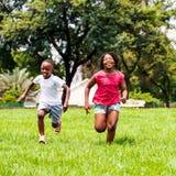 Afrikanische Kinder, die zusammen in Park laufen Stockfoto
