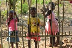 Afrikanische kleine Kinder, die nahen Zaun stehen Stockfotos