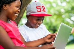 Afrikanische Knaben, die Zeit mit Laptop genießen Lizenzfreie Stockbilder