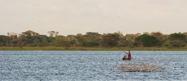 Afrikanische Leute, die einen See im Einbaum kreuzen Stockbilder