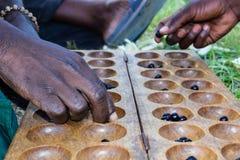 Afrikanische Männer, die ein lokales Brettspiel spielen stockfotos