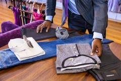Afrikanische Männer, die für Spitzen-Kleidung im gehobenen Mall kaufen stockfotos