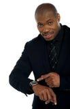 Afrikanische männliche Anzeige in Richtung zur Armbanduhr Lizenzfreies Stockbild