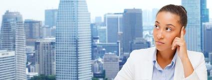 Afrikanische oben schauende und denkende Geschäftsfrau Stockfoto