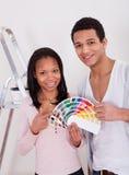 Afrikanische Paare, die Farbe für neues Haus wählen Stockbilder
