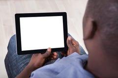 Afrikanische Person, die mit digitaler Tablette sitzt Stockbild