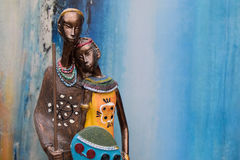 Afrikanische Statue eines Mädchens mit den jungen Männern vom ethnischen Blau mit ockerhaltigem Hintergrund hinten lizenzfreies stockbild