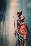 Afrikanische Statue eines Mädchens mit den jungen Männern vom ethnischen Blau mit ockerhaltigem Hintergrund hinten Lizenzfreie Stockfotografie