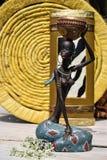 Afrikanische Statue eines Mädchens mit einem Topf auf seinem Kopf mit einem ethnischen Hintergrund hinten Stockbild
