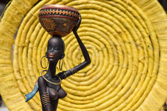 Afrikanische Statue eines Mädchens mit einem Topf auf seinem Kopf mit einem ethnischen Hintergrund hinten Lizenzfreie Stockfotografie