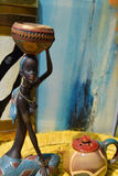 Afrikanische Statue eines Mädchens mit einem Topf auf seinem Kopf mit einem ethnischen Hintergrund hinten stockfotos