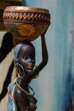 Afrikanische Statue eines Mädchens mit einem Topf auf seinem Kopf mit einem ethnischen Hintergrund hinten Stockfoto