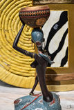 Afrikanische Statue eines Mädchens mit einem Topf auf seinem Kopf mit einem ethnischen Hintergrund hinten stockfotografie