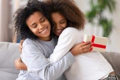 Afrikanische Tochter, die Mutter mit der relativen Leuteumfassung des Geburtstages beglückwünscht lizenzfreies stockfoto