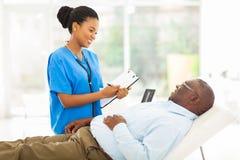 Afrikanischer Doktor, der älteren Patienten konsultiert Stockfoto