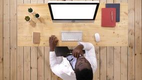 Afrikanischer Doktor, der etwas auf dem Schirm des Computers aufpasst Wei?e Bildschirmanzeige stockbilder