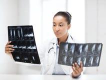 Afrikanischer Doktor, der Röntgenstrahlen betrachtet Stockfotografie