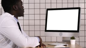 Afrikanischer Doktor, der Videoanruf mit seinem Computer macht Weiße Bildschirmanzeige stockbild