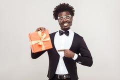 Afrikanischer Geschäftsmann, der Finger auf Geschenkbox zeigt lizenzfreies stockfoto
