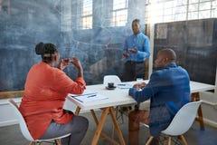 Afrikanischer Geschäftsmann, der Fragen von den Mitarbeitern während der Darstellung vorbringt Lizenzfreie Stockfotos