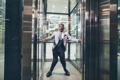Afrikanischer Geschäftsmann, der im Aufzug schreit Furchtplatzangstkonzept lizenzfreie stockfotografie