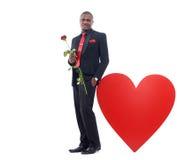 Afrikanischer Geschäftsmann, der vom großen Herzen aufwirft und sich lehnt Stockfotografie