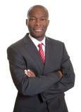 Afrikanischer Geschäftsmann mit den gekreuzten Armen lächelnd an der Kamera Stockfoto