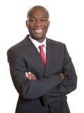 Afrikanischer Geschäftsmann mit den gekreuzten Armen lachend über Kamera Lizenzfreie Stockfotografie