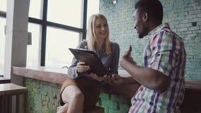 Afrikanischer Geschäftsmann und kaukasische Geschäftsfrau, die im modernen modischen Büro, Dokumente zusammen betrachtend sitzt Stockfoto