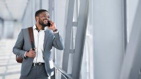 Afrikanischer Gesch?ftsmann Walking Inside Airport und Unterhaltung am Telefon lizenzfreie stockfotos