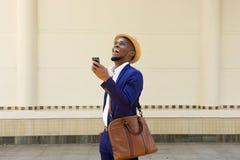 Afrikanischer Geschäftsmann, der mit einem Mobiltelefon und einer Tasche geht Lizenzfreie Stockfotos