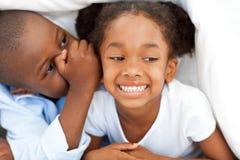 Afrikanischer Junge, der etwas zu seiner Schwester flüstert Stockbilder