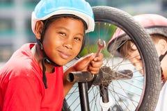 Afrikanischer Junge, der Fahrradfelge mit Schlüssel repariert Lizenzfreie Stockfotografie