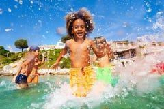 Afrikanischer Junge, der mit Freunden im seichten Wasser spielt stockbild
