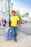 Afrikanischer Junge, der rosa Gepäck und das Gehen hält Stockbild