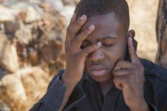 Afrikanischer Junge am Handy Stockbild
