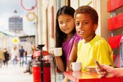 Afrikanischer Junge und asiatisches Mädchen, die draußen im Café sitzt Stockfotografie