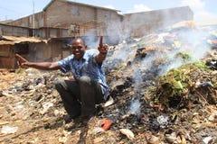 Afrikanischer junger Mann sitzt und lächelt auf einem Berg des Abfalls stockfoto