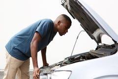 Afrikanischer Kerl, der unter der Haube von seinem aufgegliedertes Auto schaut Stockfoto