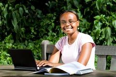Afrikanischer Kursteilnehmer, der draußen studiert Stockbild