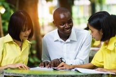 Afrikanischer Lehrer, der asiatischen Studenten über Fremdsprachen unterrichtet lizenzfreie stockbilder